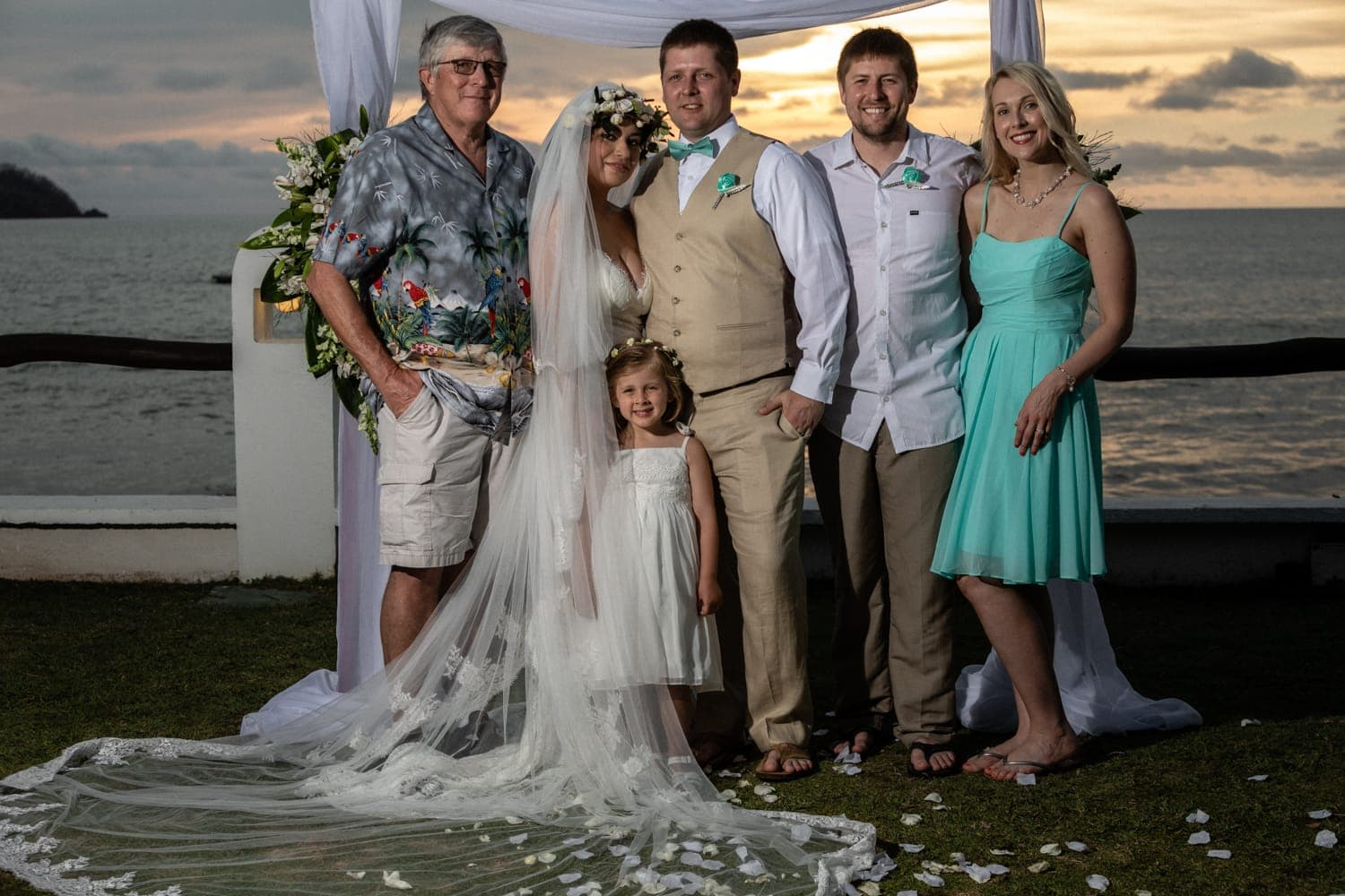 Beach portrait of bride, groom, and family at sunset in Guanacaste.