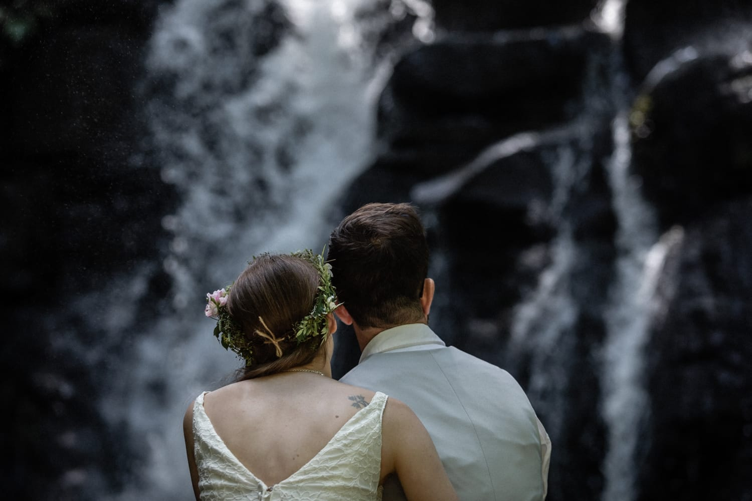 Just married couple sitting on log looking at waterfall.