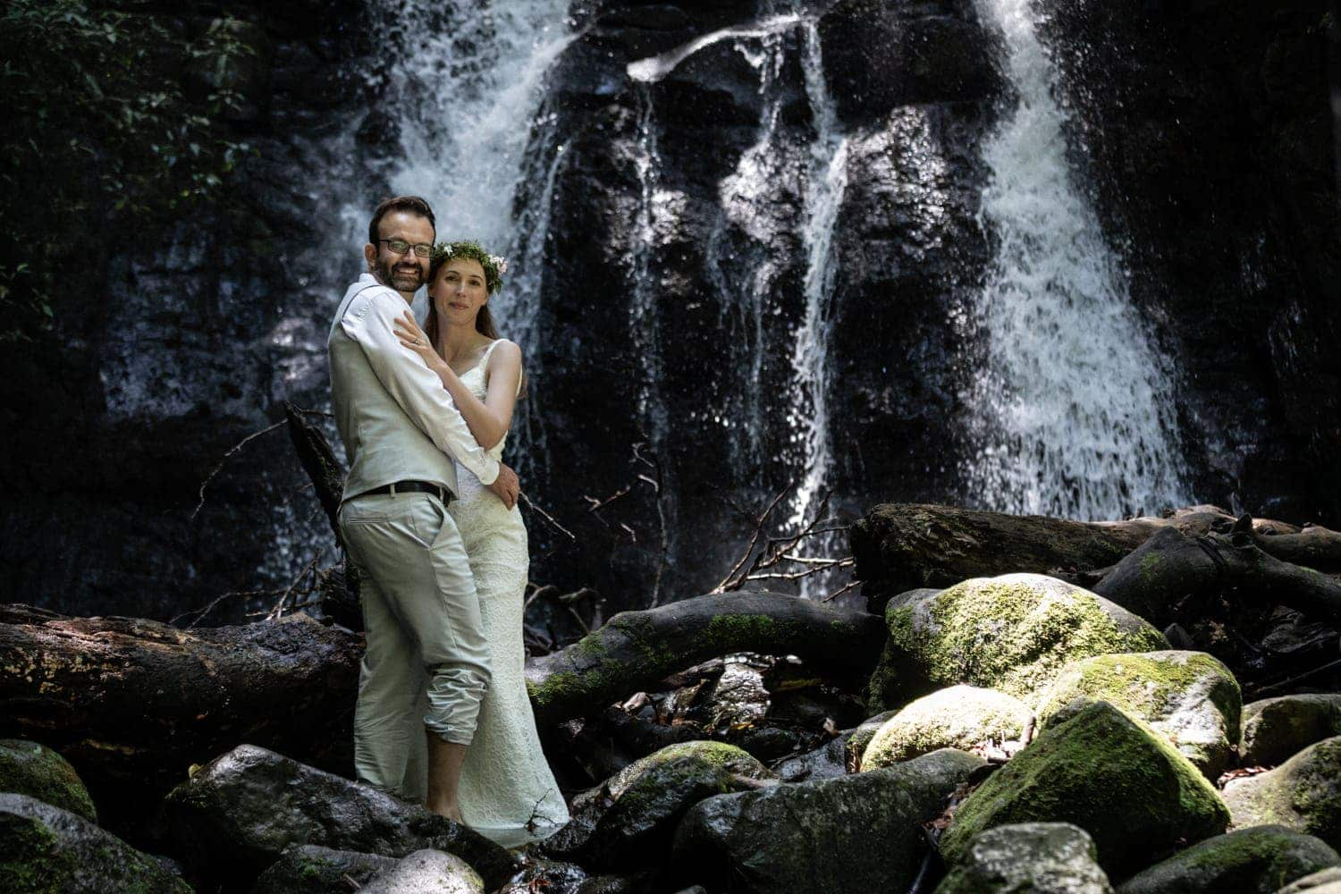 Couple stands in font of waterfall for wedding photos.