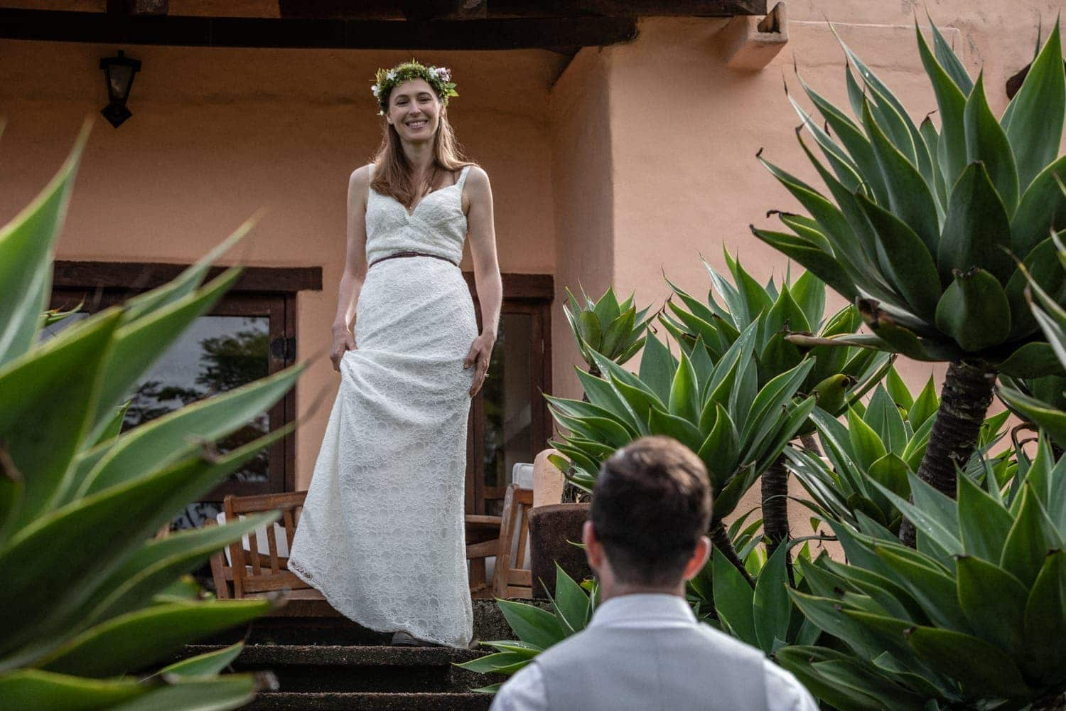 Bride in white wedding dress walks down stairs in tropical garden.