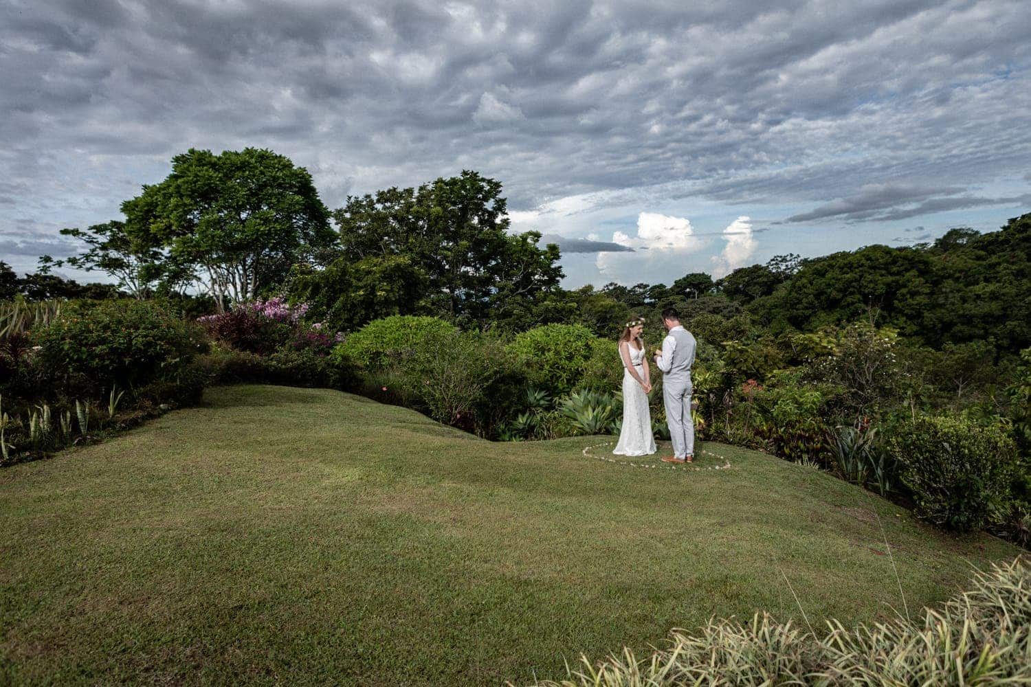 Wide angle photo of couple getting married in tropical garden.