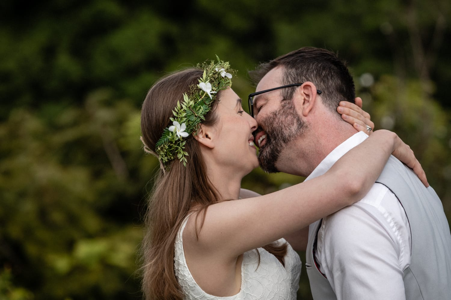 Couple getting married in tropical garden kisses.