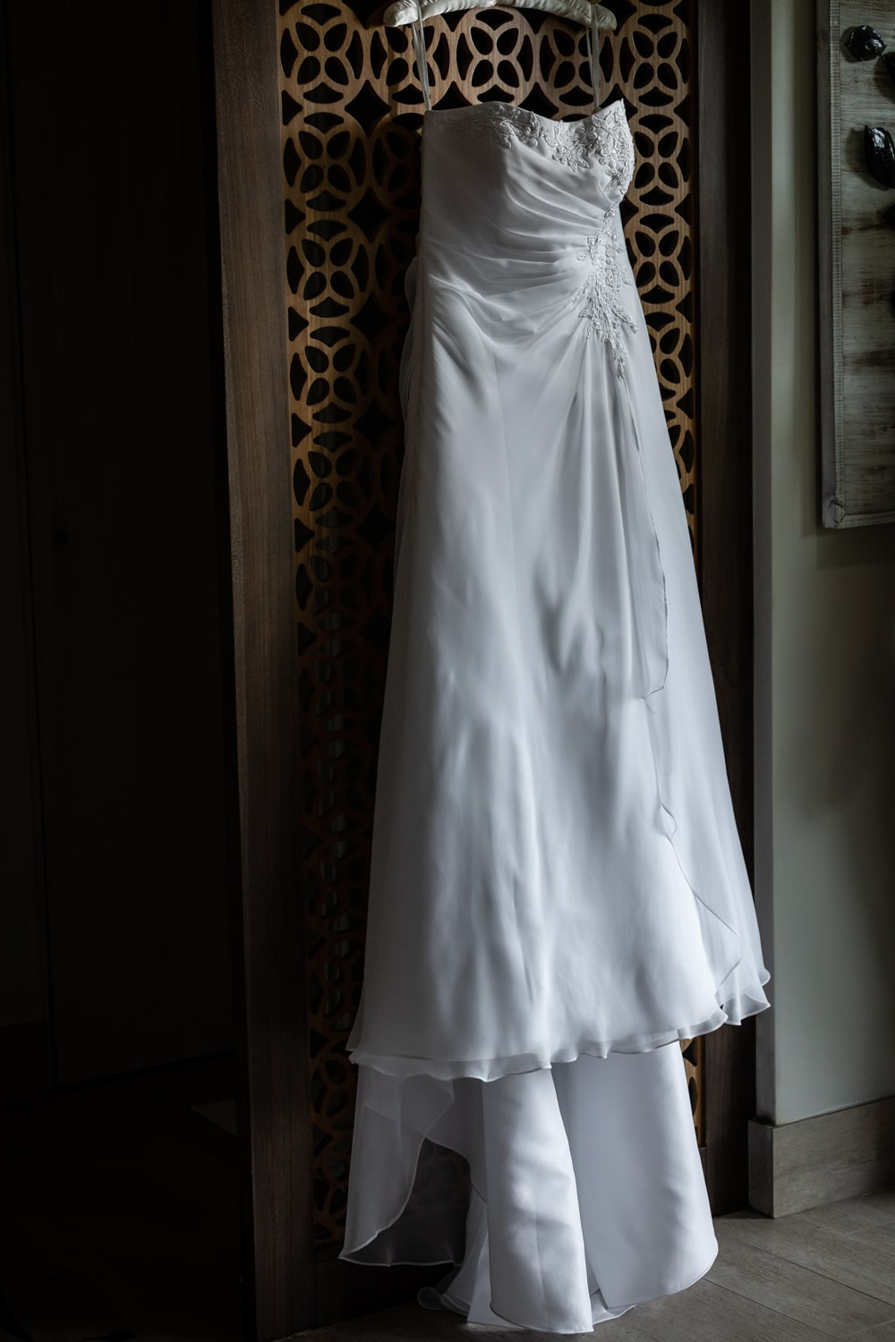 White wedding dress on ornate wooden wall in Secrets Papagayo bridal suite.