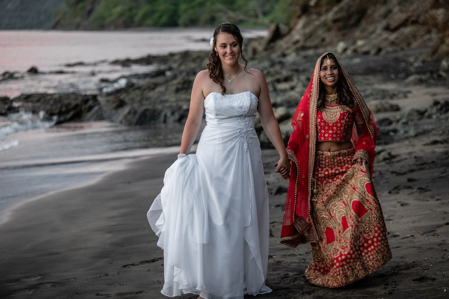 Beautiful brides holding hands and walking on beach in Guanacaste at sunset.