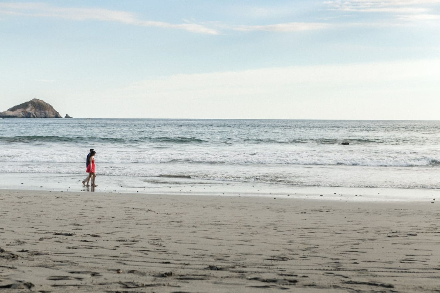 Couple holding hands walk on beach for Costa Rica engagement photos.