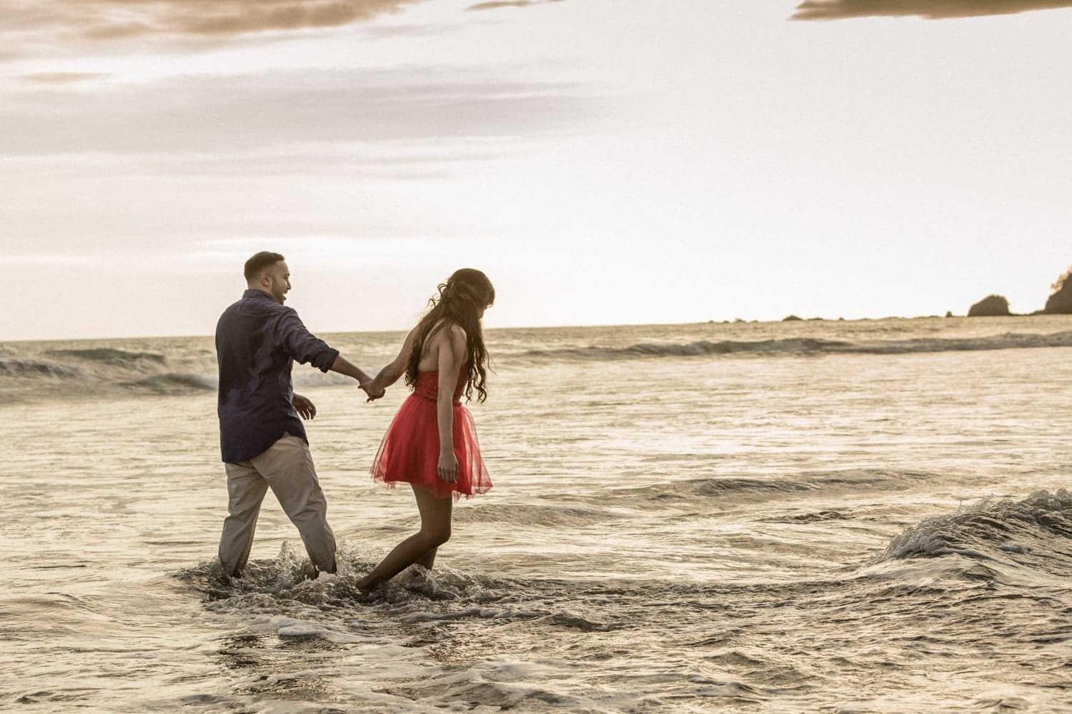 Couple having fun in the water at Manuel Antonio Beach in Costa Rica during engagement session.