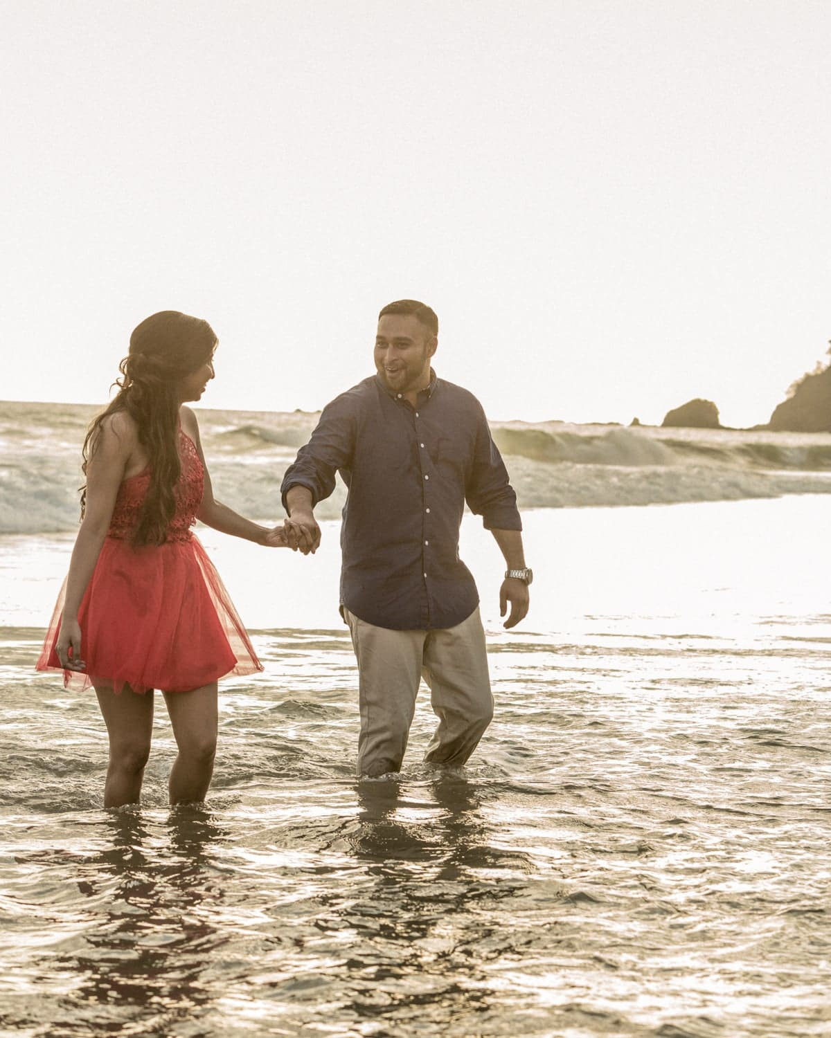 Couple in love holding hands and walking in water at the beach.