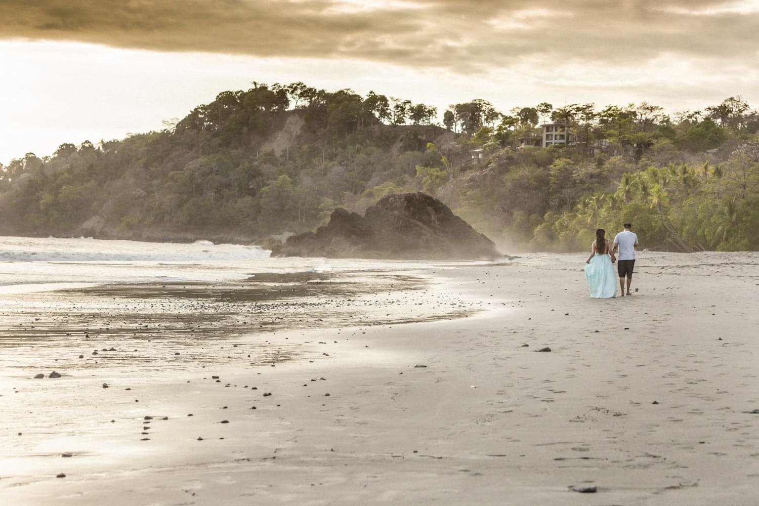 Panoramic photo of just engaged couple walking on beach at sunset.