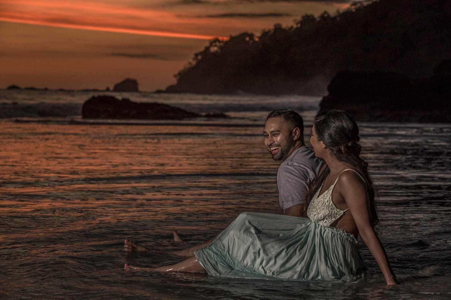 Warm sunlight from setting sun bathes couple in love on beach.