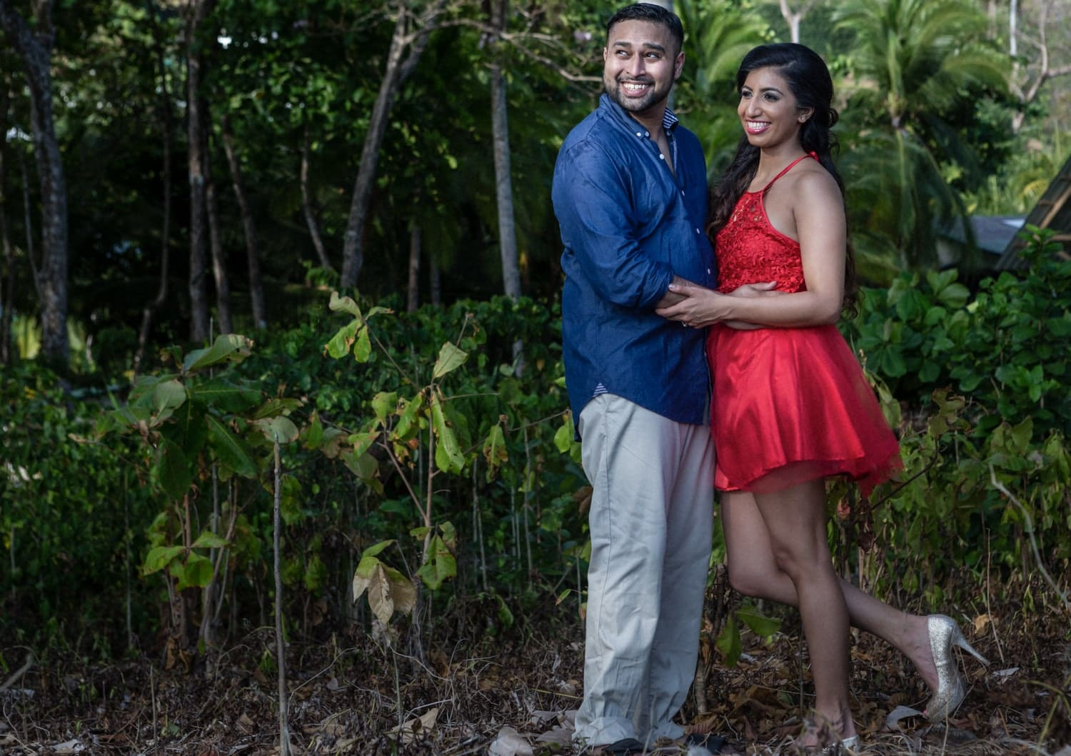Lovers in casual clothing in Costa Rica rainforest while getting engaged.