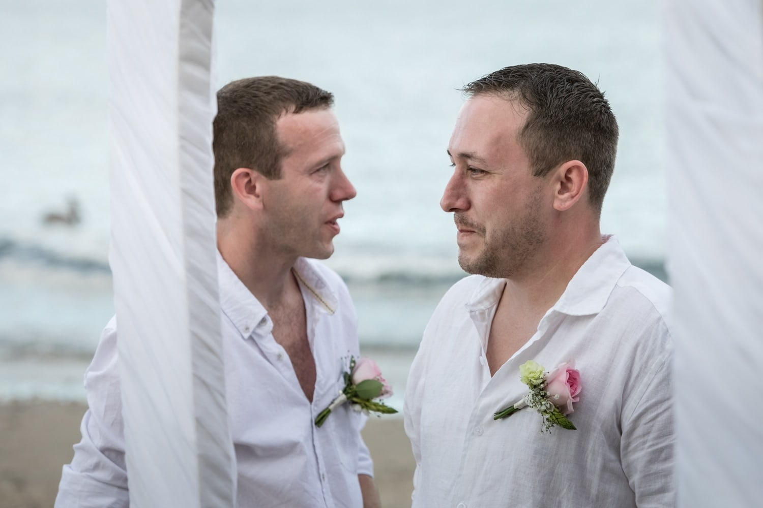 Emotional groom waiting at altar with best man as bride approaches.