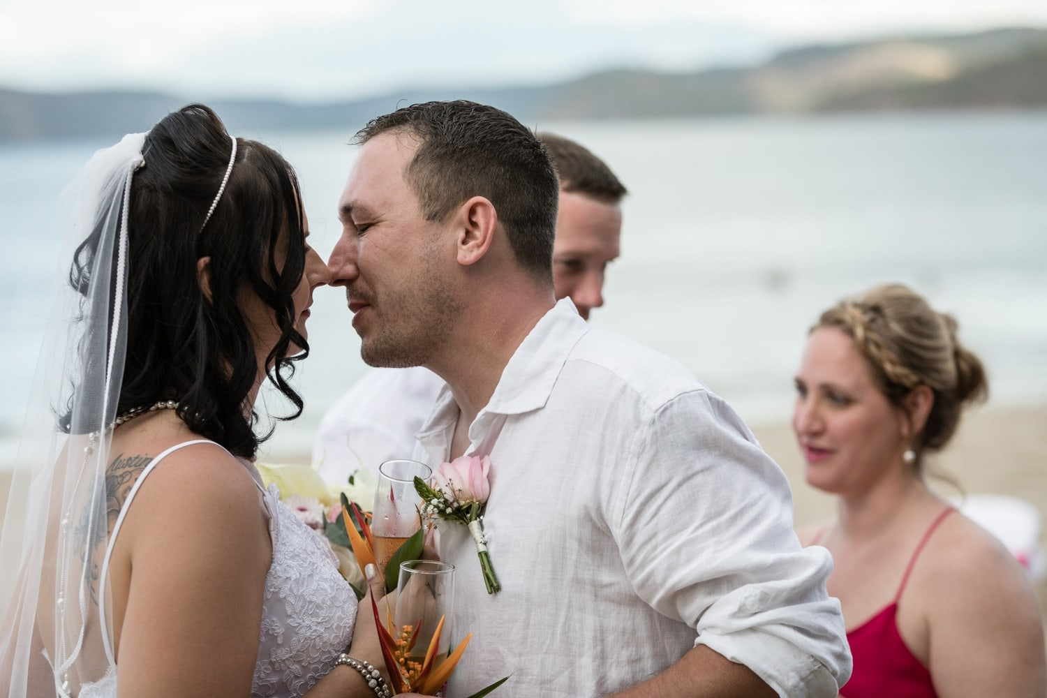 Bride and groom about to kiss after saying vows on beach.