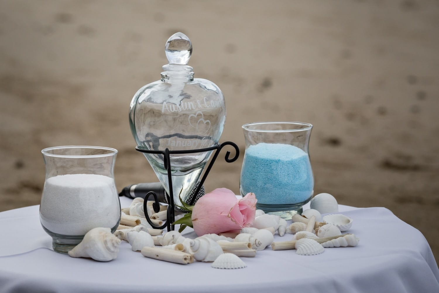 Glasses filled with white and blue sand for wedding ceremony ritual.