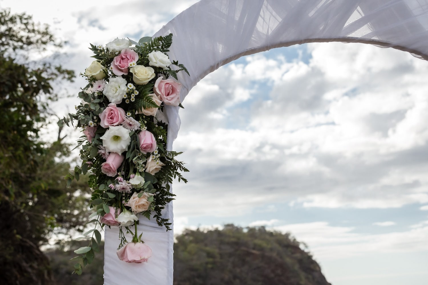 Wedding ceremony arch on beach decorated with gorgeous floral bouquet.