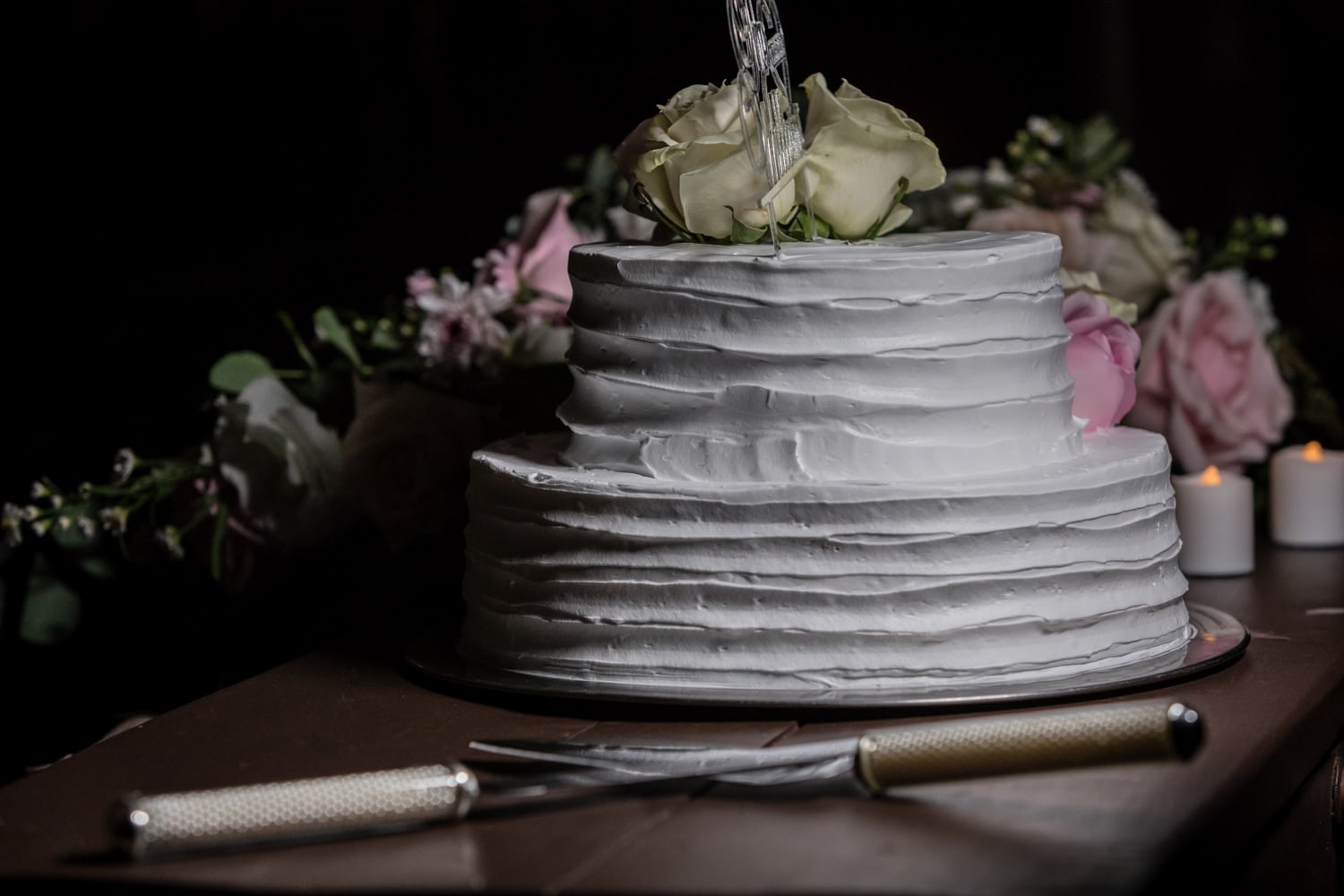 Wedding cake with ornate flowers with cutting utensils on wood table.