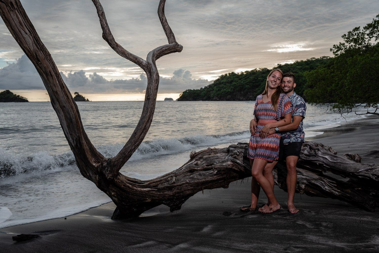 Couple on a weathered tree on Las Catalinas Beach in Guanacaste just after sunset for their engagement photos.