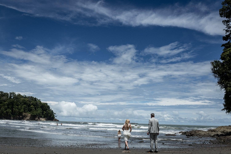 A bride and groom have a bit of fun on Playa Ventanas Beach in Ojochal in Puntarenas, Costa Rica.