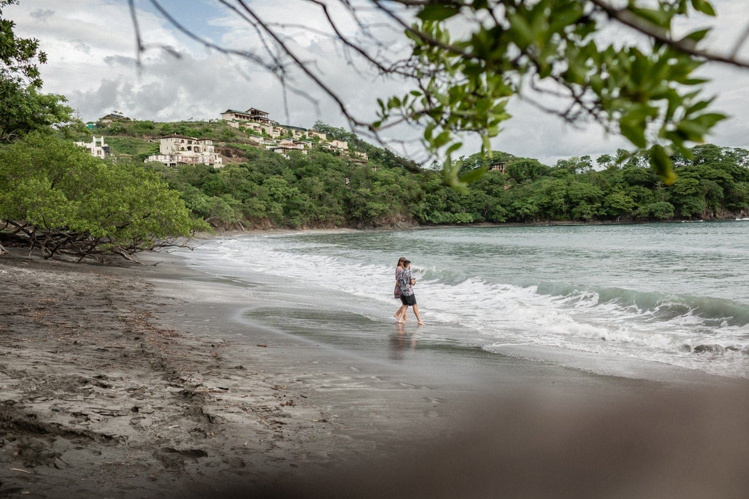 Photo of couple walking on the beach during engagement session in Costa Rica.
