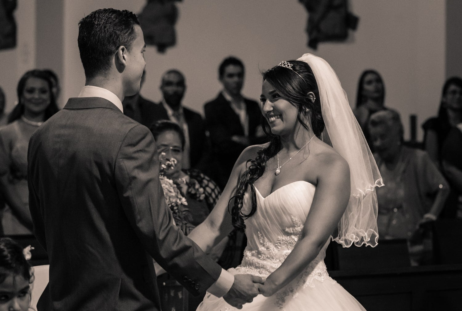 Bride and groom standing at altar and holding hands.