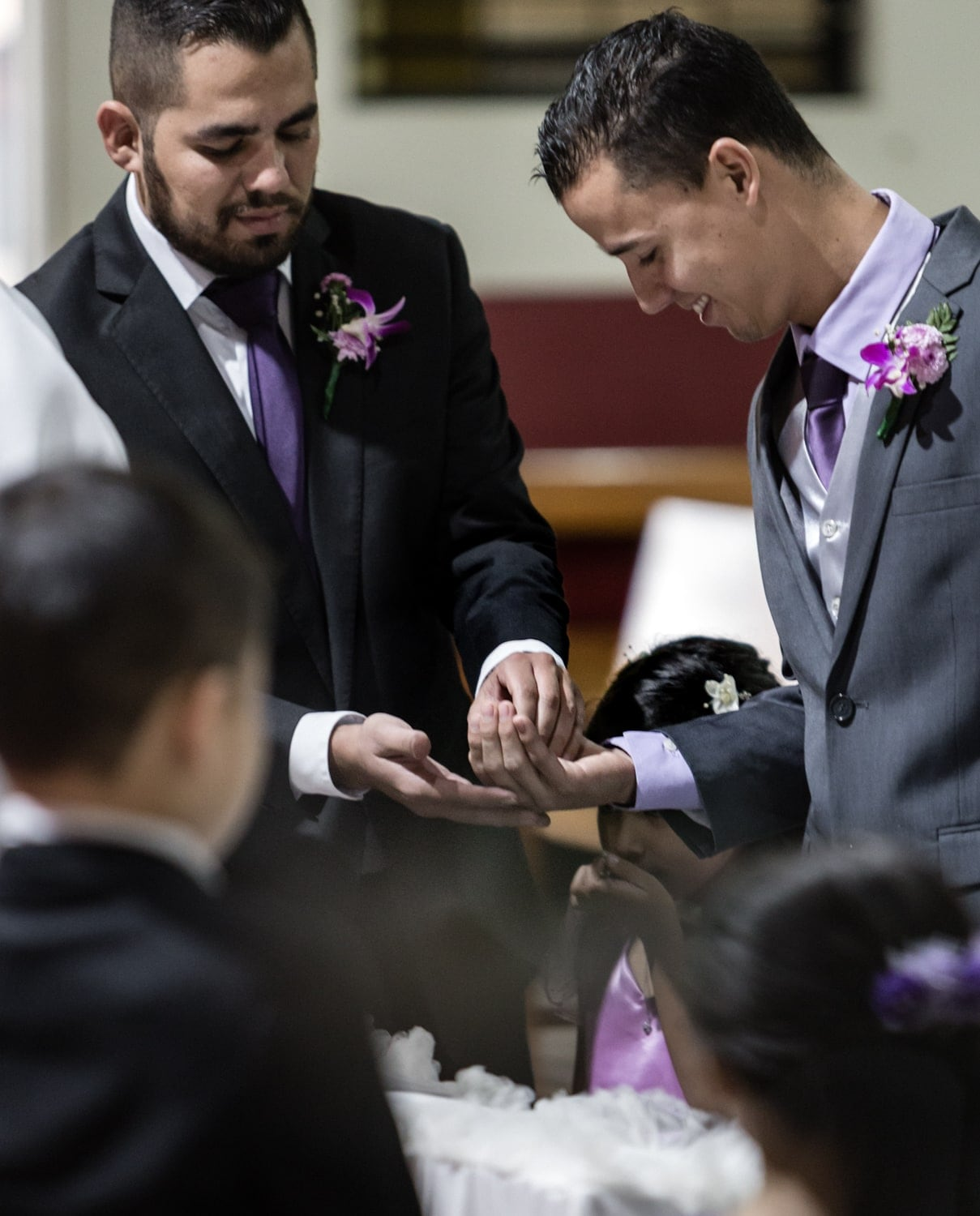 Ring bearer gives wedding bands to groom during wedding ceremony.