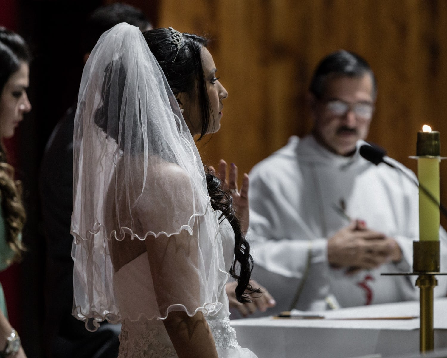 Bride wearing white veil watches as witnesses sign documents.