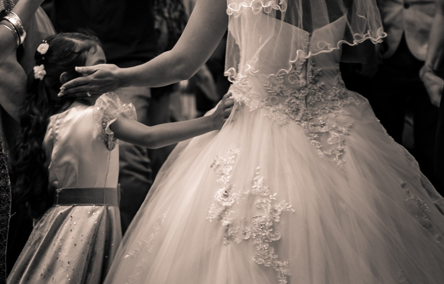 Black and white photo of bride and flower girl sharing a moment.