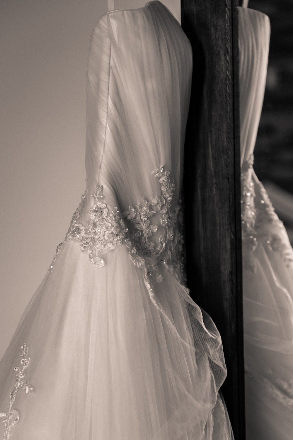 Photo of wedding dress handing from mirror during bridal preparation.