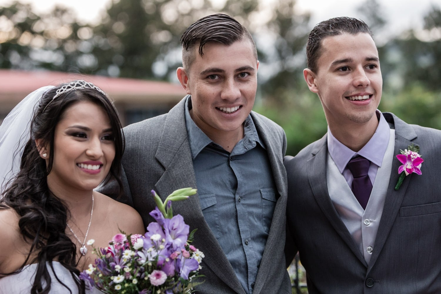 Bride and groom pose for photo with groomsman.