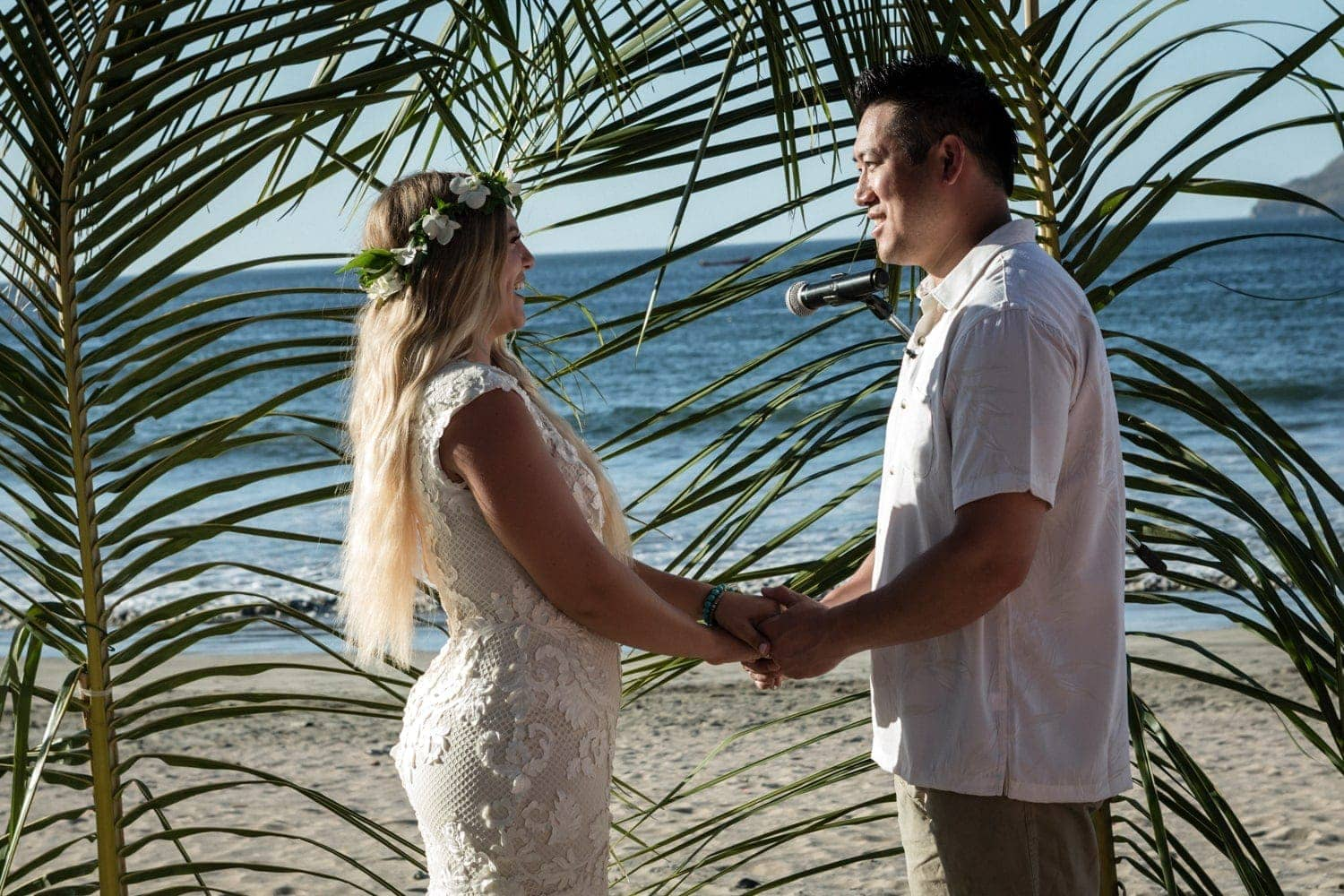 Bride and groom stand an tropical altar during beach wedding ceremony.