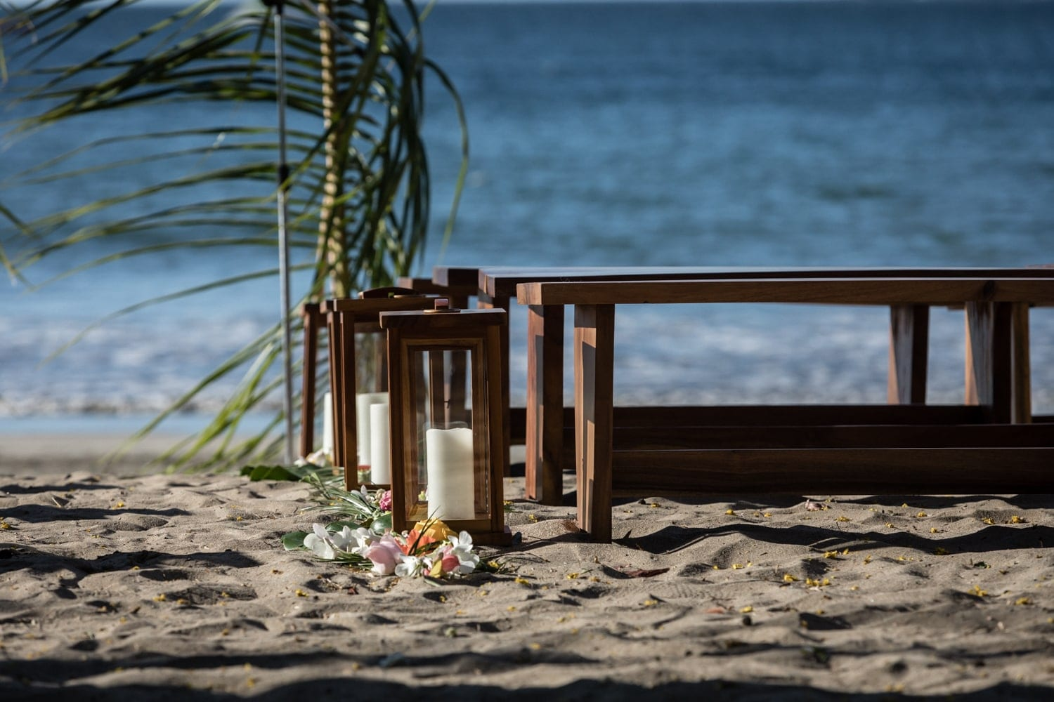 Tropical flowers and candles line aisle at wedding venue on Tamarindo beach.