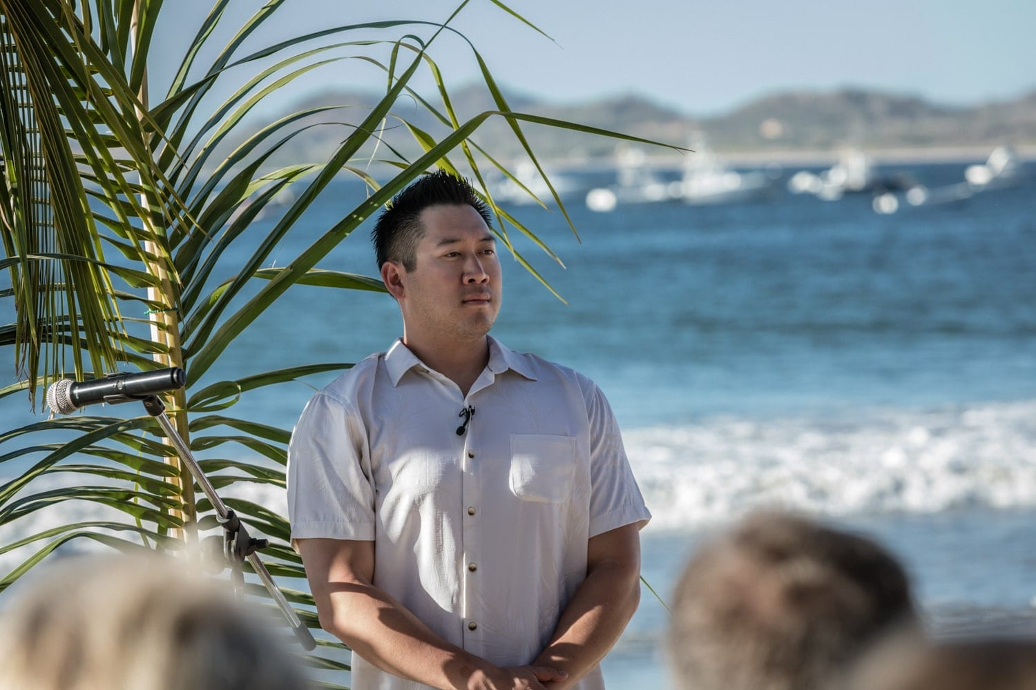 Groom waits at altar on beach in Tamarindo for bride to arrive.