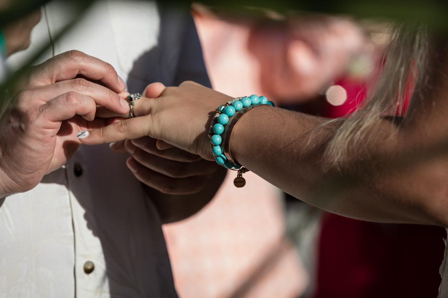 Bride and groom exchange rings during beach wedding ceremony.