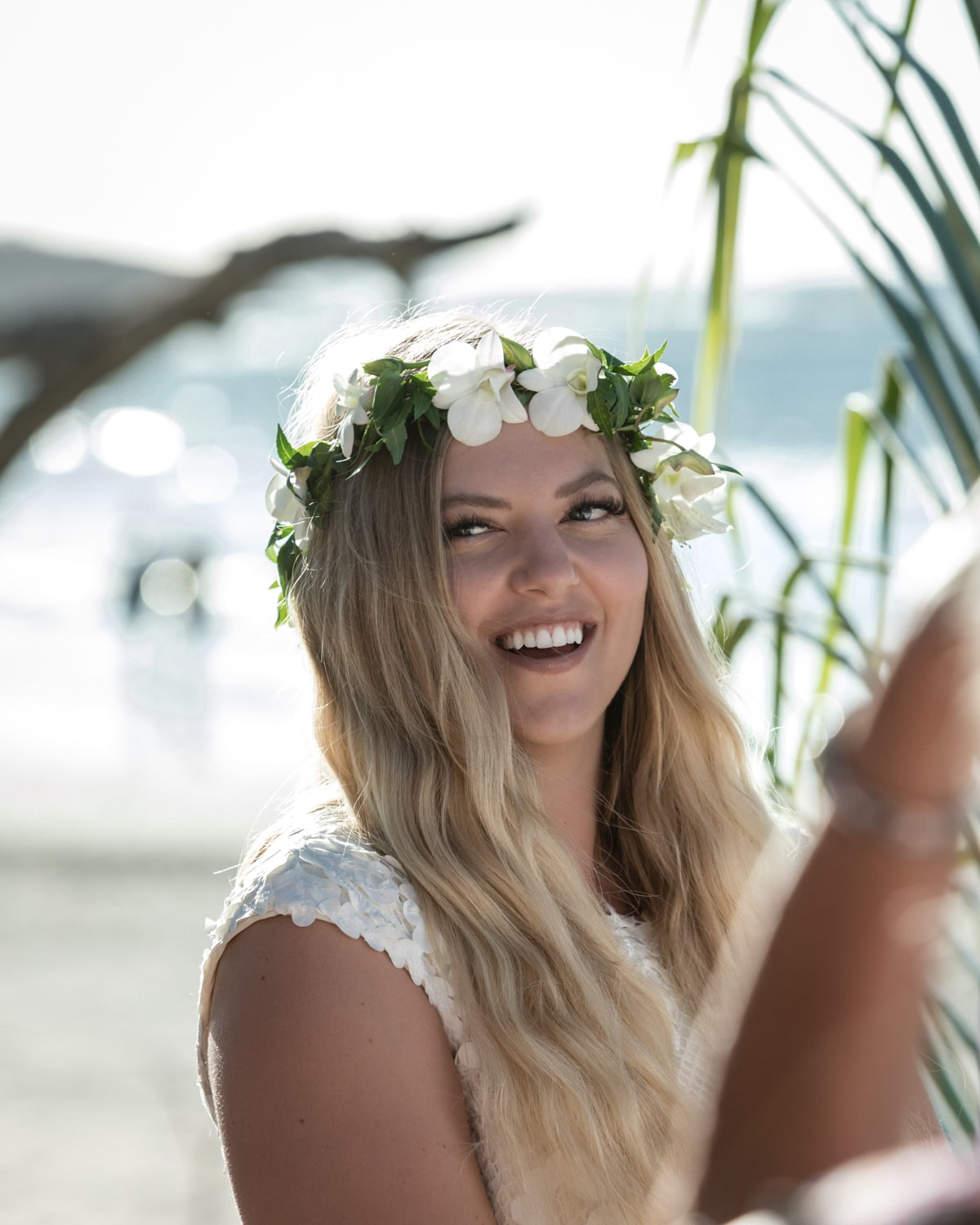 Bride wearing crown with white flowers smiles during beach wedding ceremony.