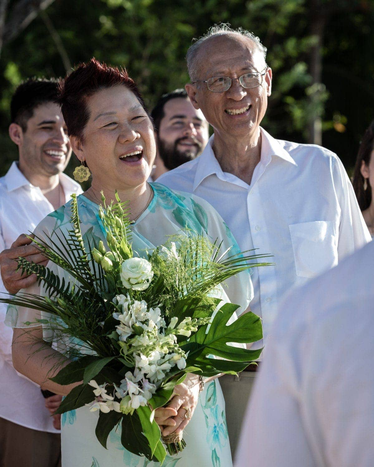 Grooms parents smile as they watch their son's beach wedding ceremony in Costa Rica.