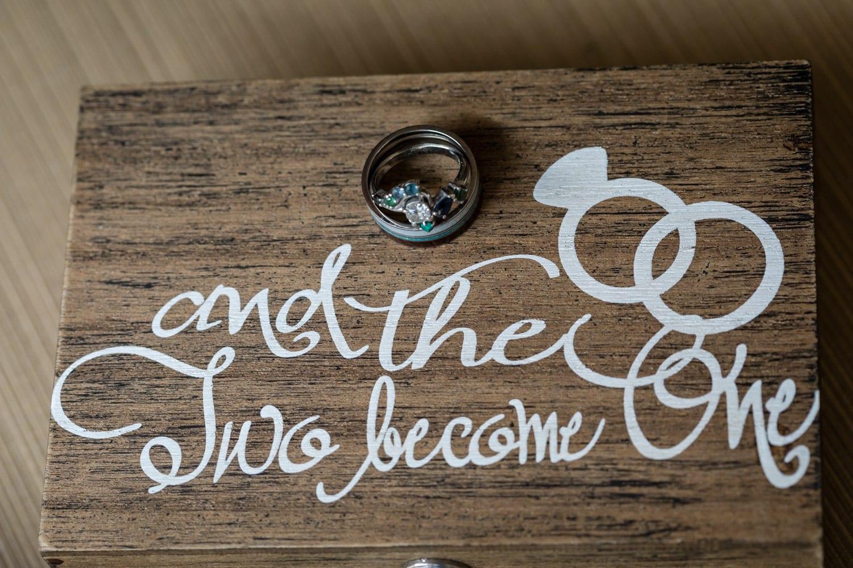 Bride & Groom wedding rings on wooden ring box.