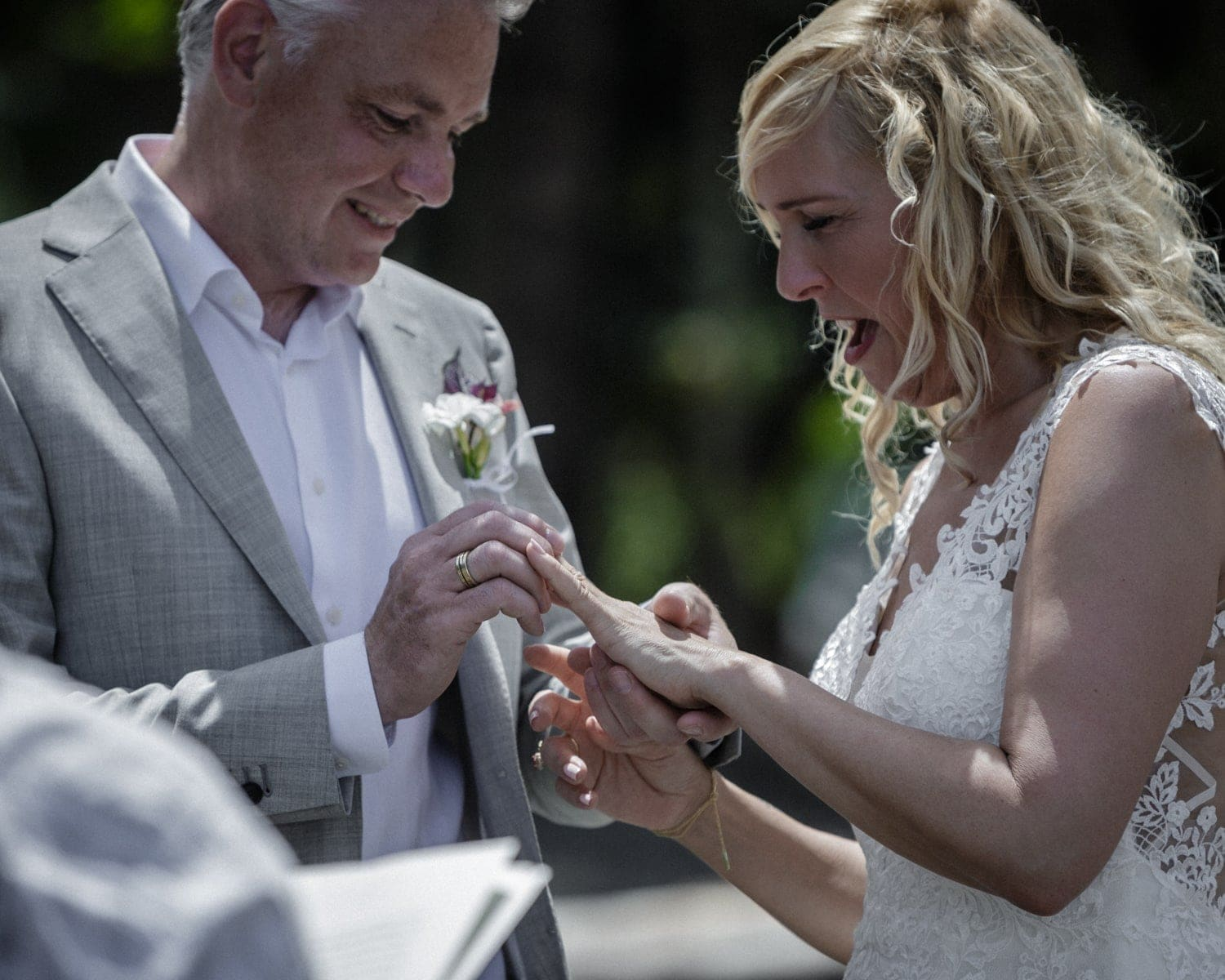 Groom puts ring on brides finger during beach wedding in Costa Rica.