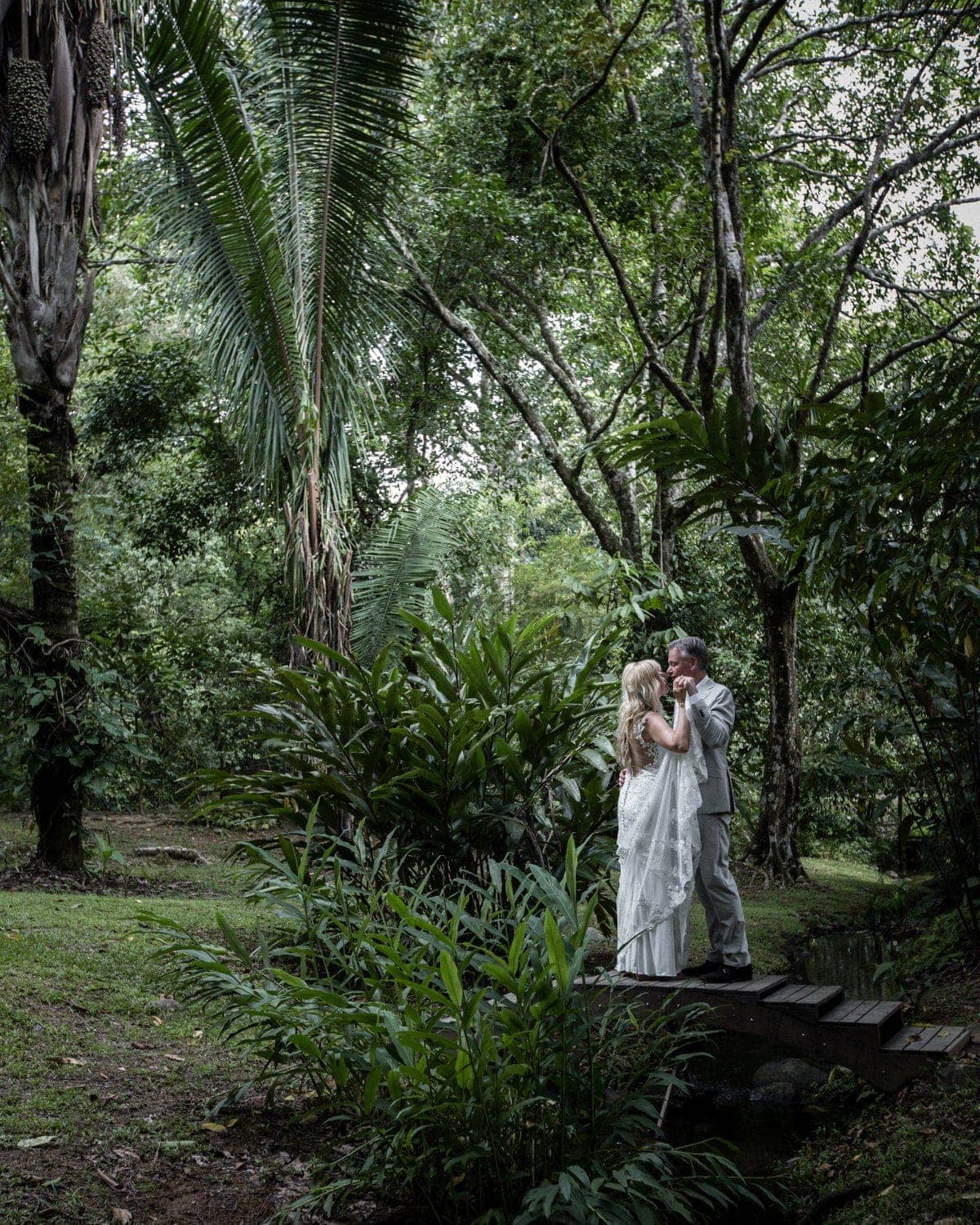 Just married couple pose for a photo in tropical garden in Costa Rica.