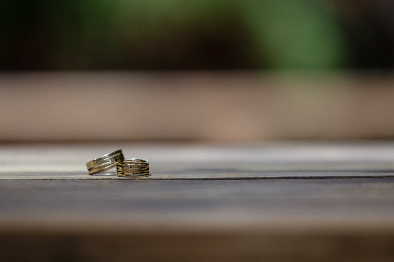 Gold wedding bands on wood table in tropical garden.
