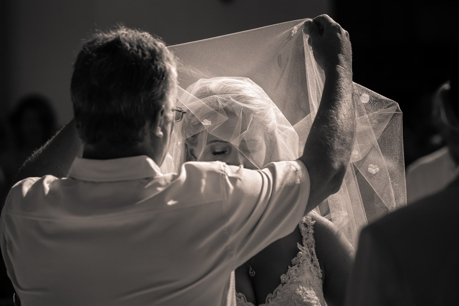 Father lifts veil from brides face after walking her to altar.