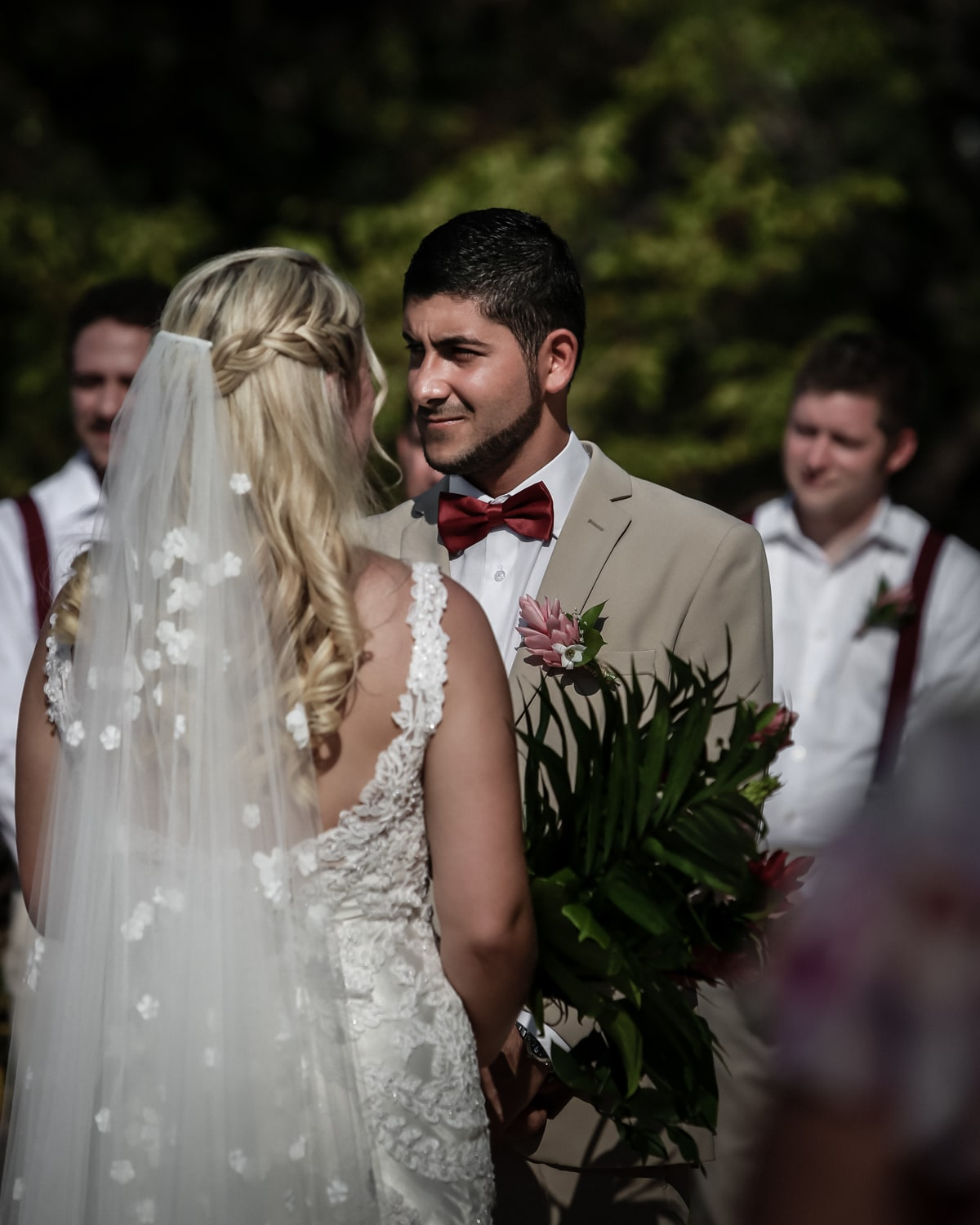 Bride with veil in hair stands at altar with husband.