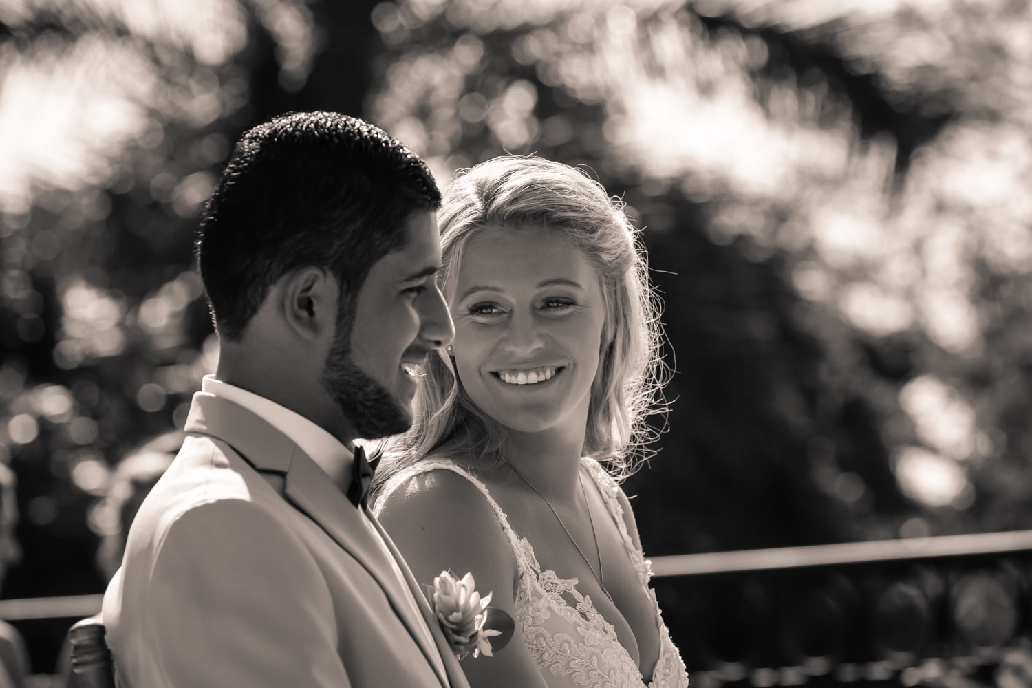 Bride smiles at groom while sitting during wedding ceremony.