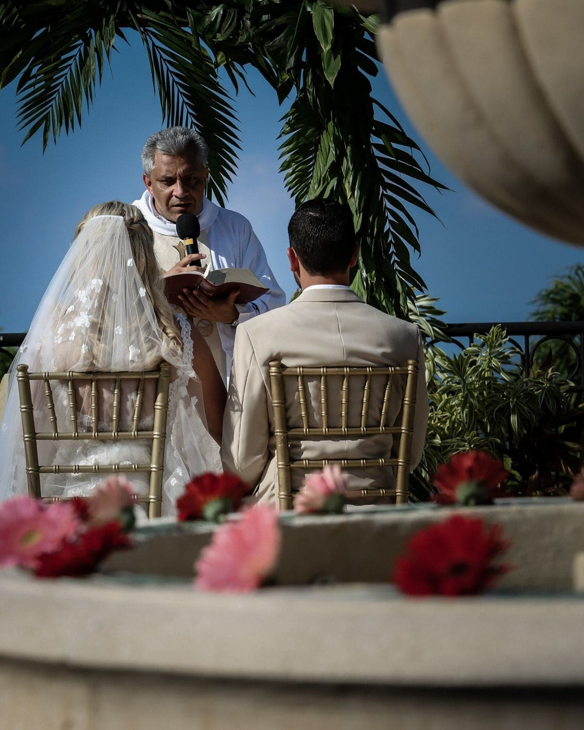 Bride and groom seated at altar during Catholic wedding ceremony.