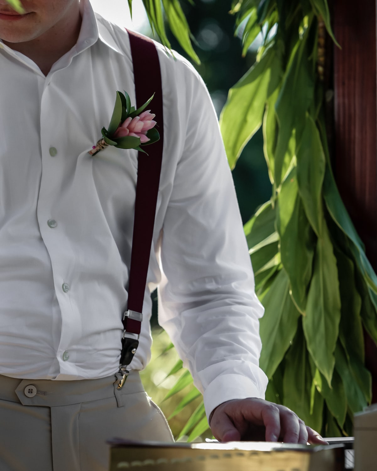 Groomsman wearing exotic boutonniere places and on Bible.