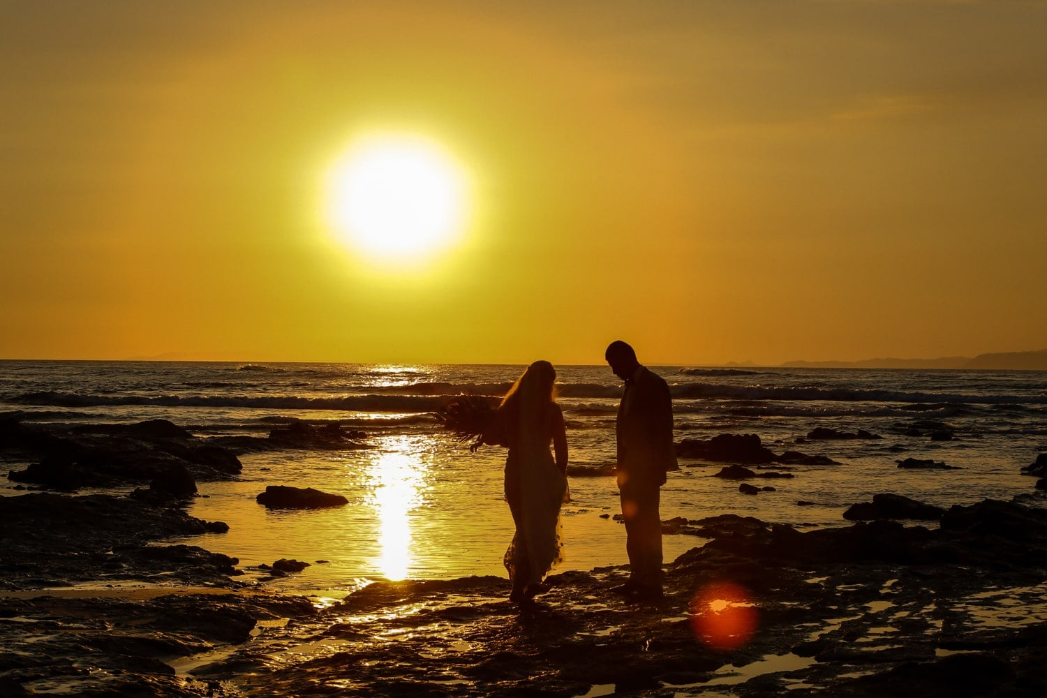 Bride and groom on beach at Punta Leona at sunset in Costa Rica.