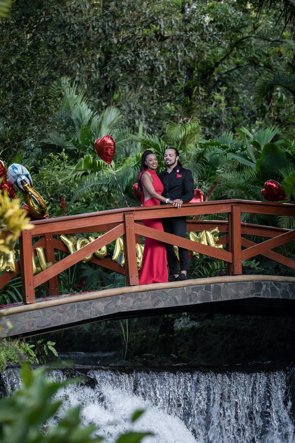 Just engaged couple stands on bride above waterfall at Tabacon Resort.