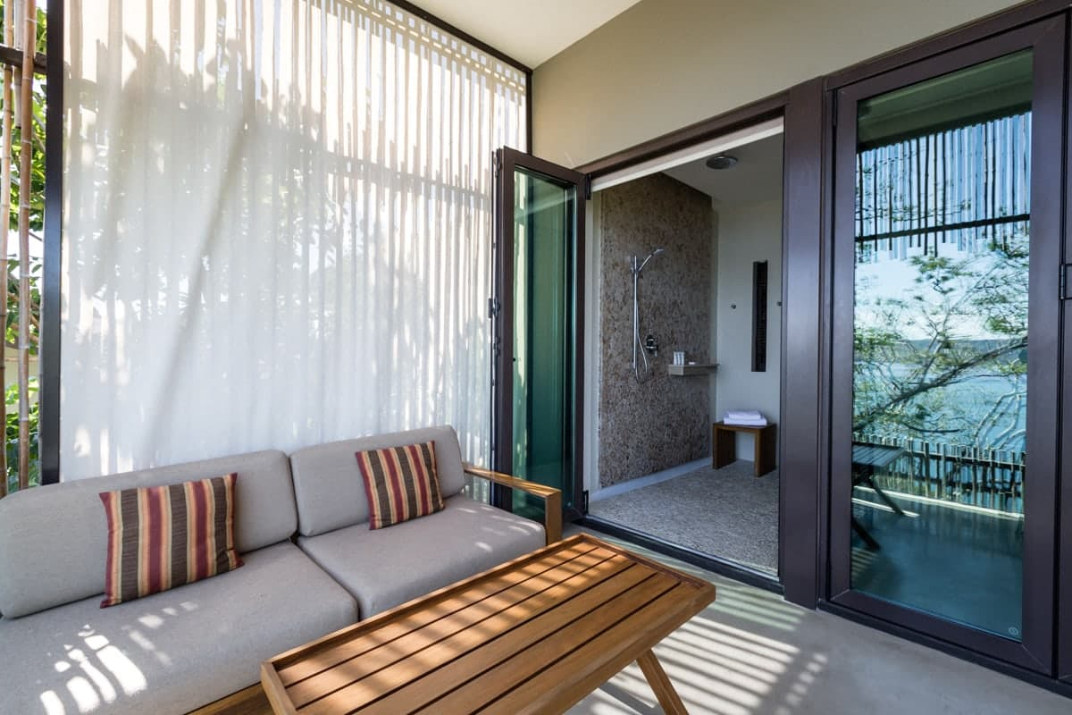 Balcony with chairs just outside walk-in shower.