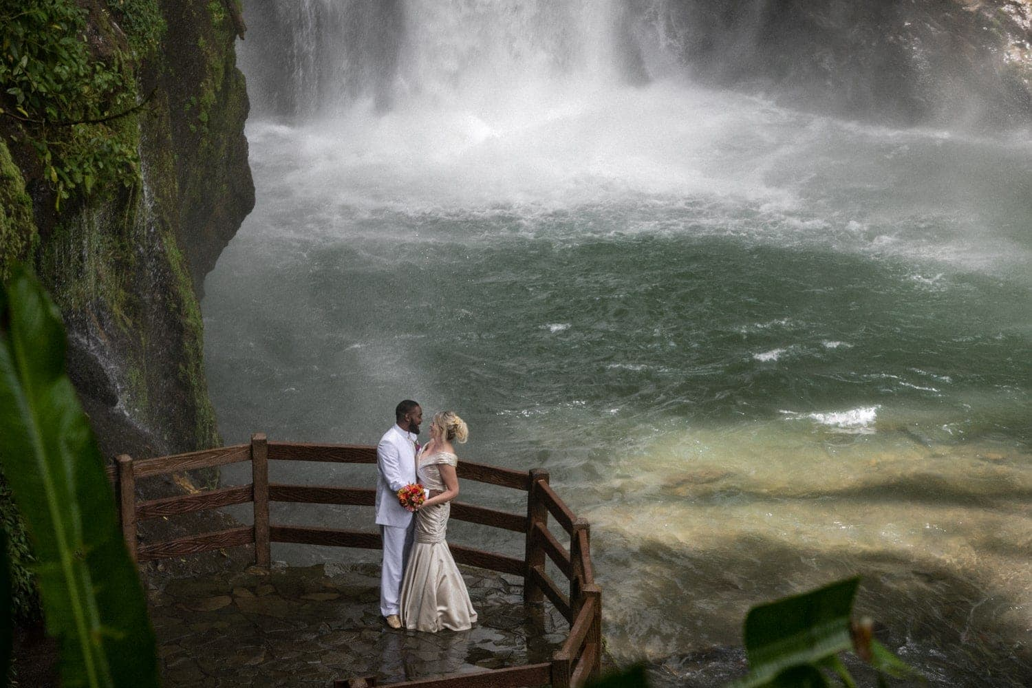 Dramatic photo of bride and groom near base of waterfall after wedding ceremony.