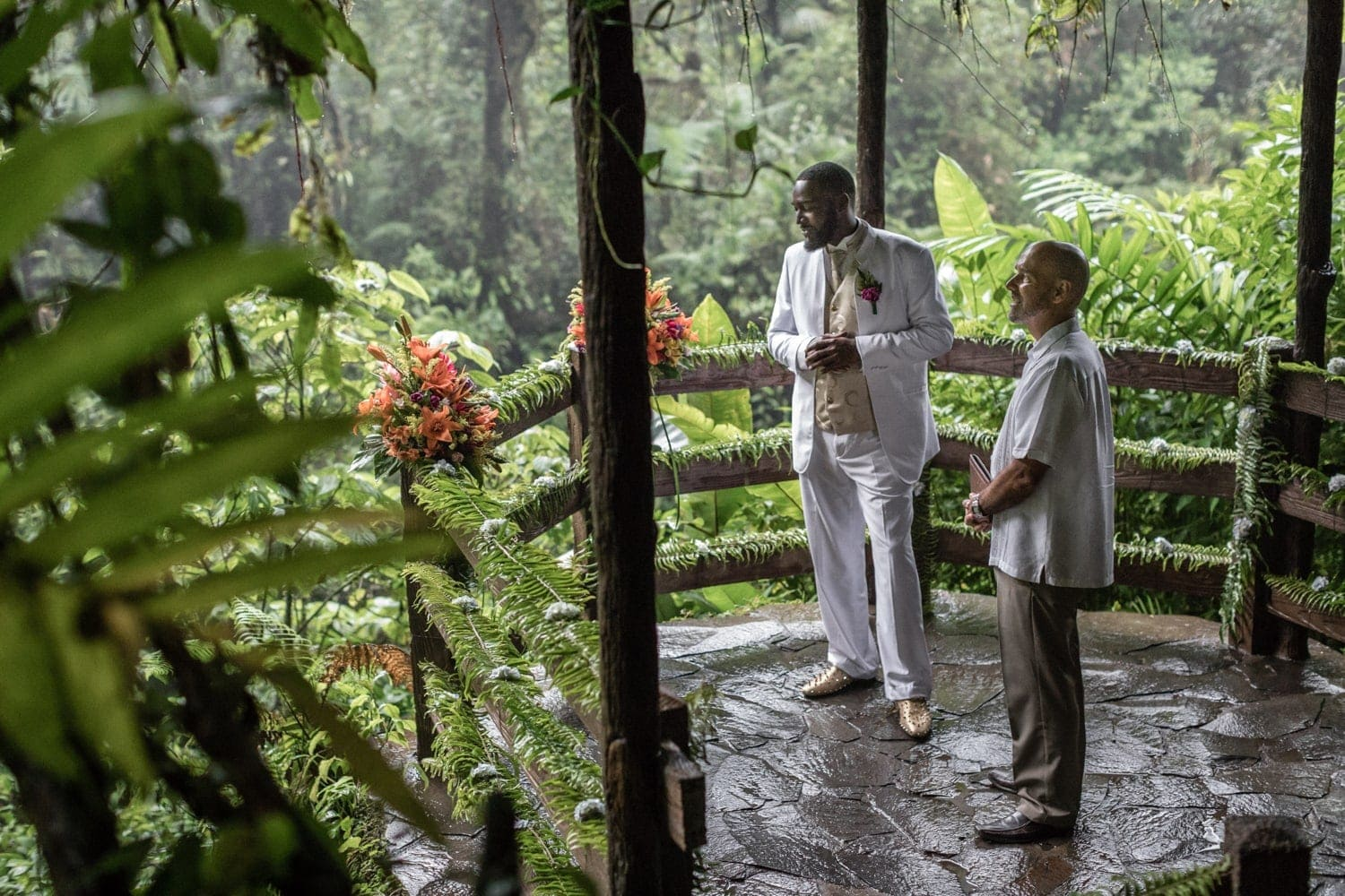 Groom waits for bride with officiant at wedding venue at La Paz Waterfall Gardens.