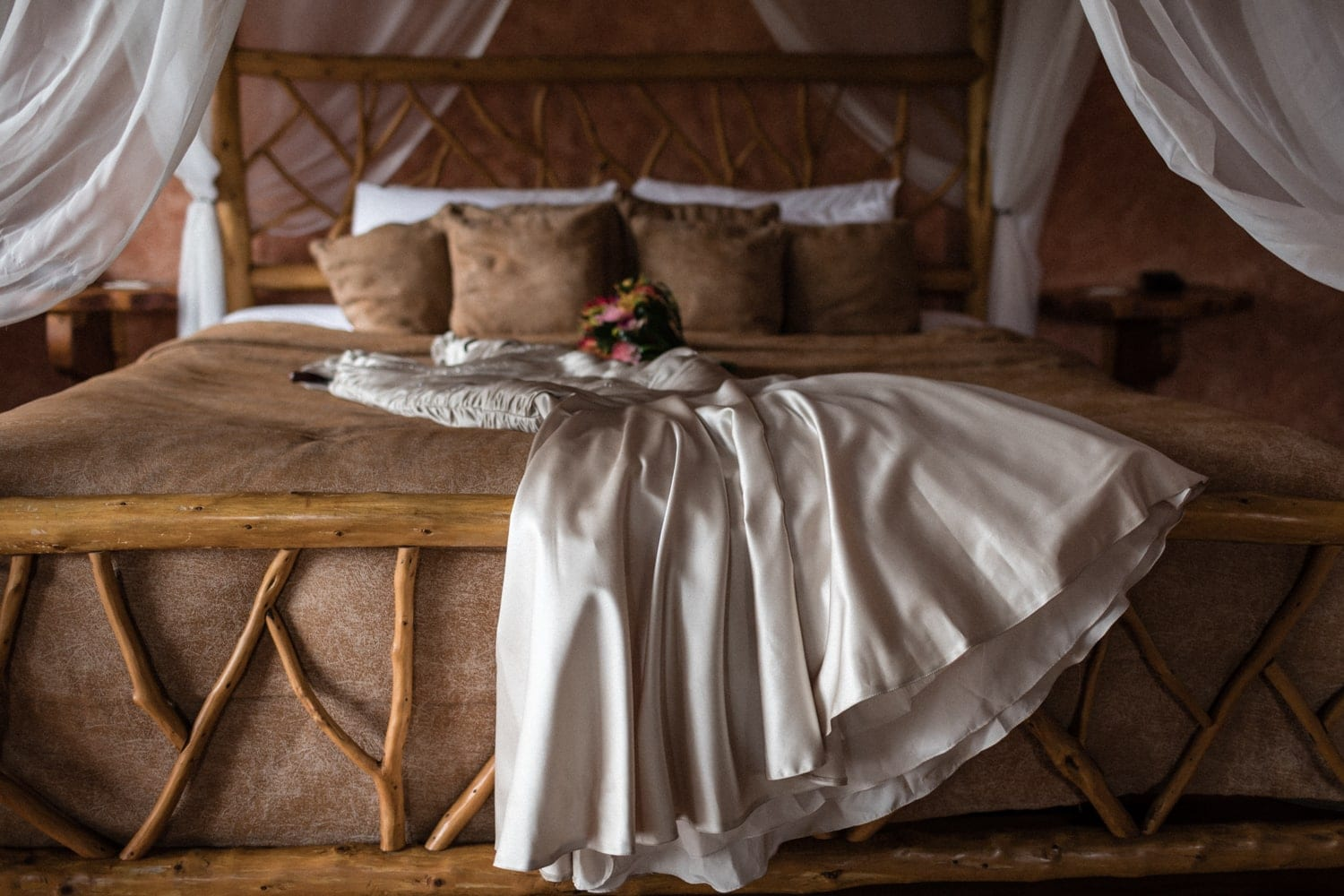 Wedding dress on canopy bed in honeymoon suite at Peace Lodge in Costa Rica.