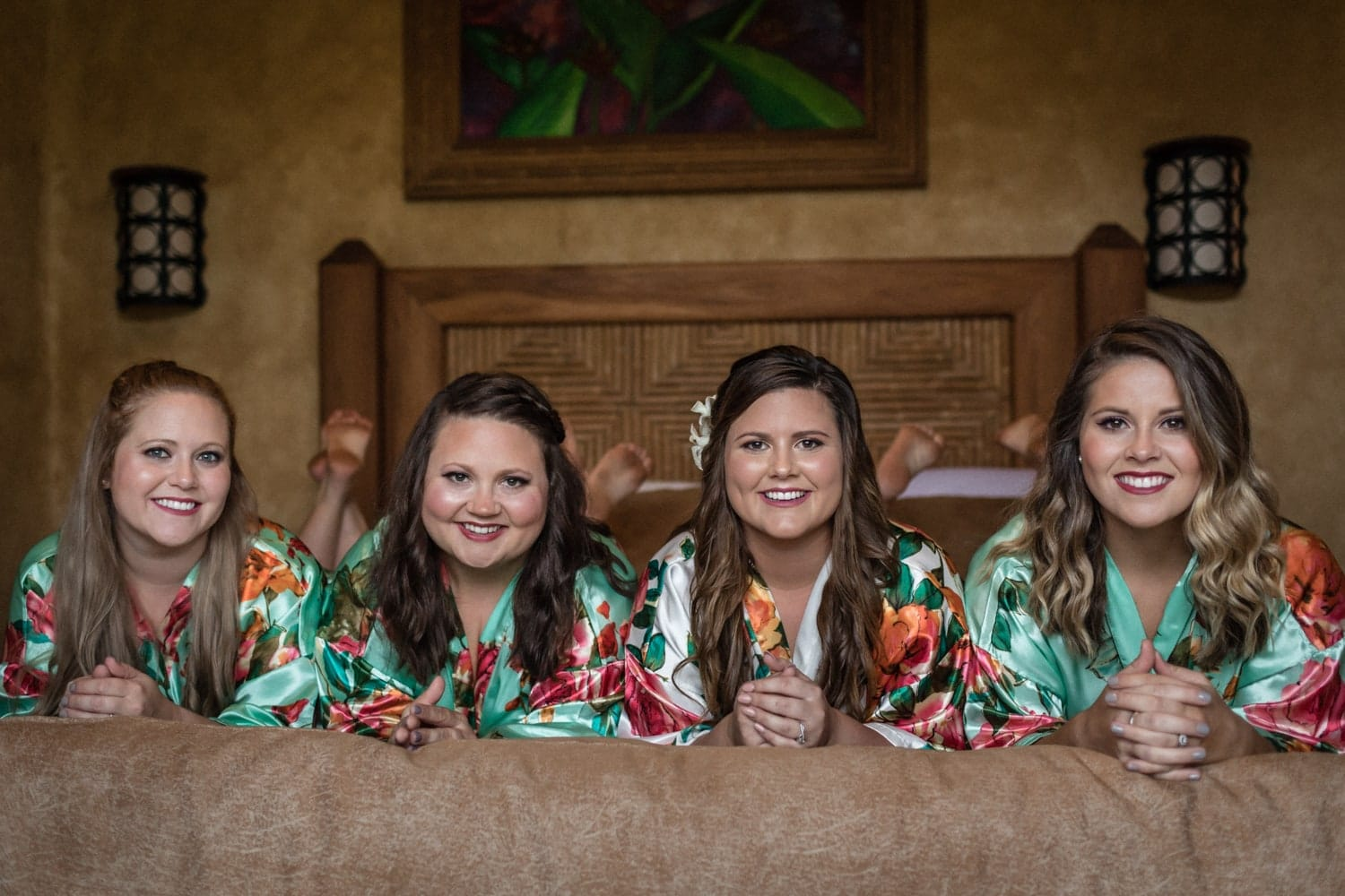 Bride and bridesmaids smiling on bed while preparing for wedding.